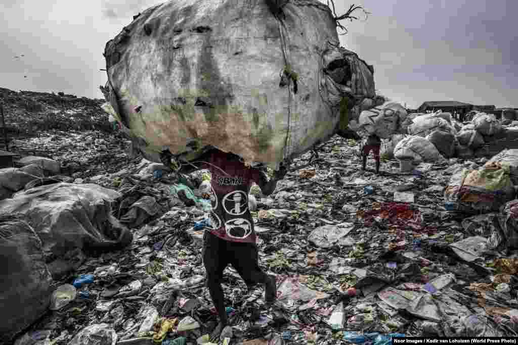 """Номинация: """"Окружающая среда"""". Фоторепортаж Кадир ван Лохайзен из Нидерландов работал в Лагосе (Нигерия). Эту фотографию он сделал на мусорном полигонеОлусосун, куда ежедневно поступаетболее 3000 тонн отходов. На территории полигона живут более 4000 человек, которые вручную собирают мусор на переработку или продажу."""