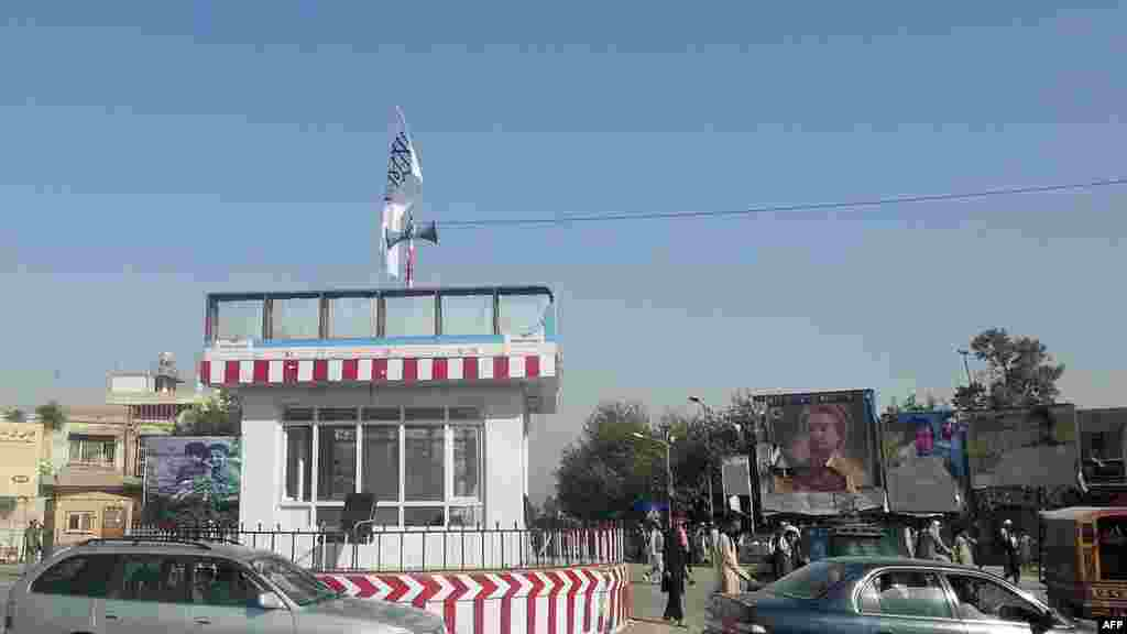 A Taliban flag flutters over the main traffic roundabout in Kunduz on September 29, a day after the insurgents overran the city.