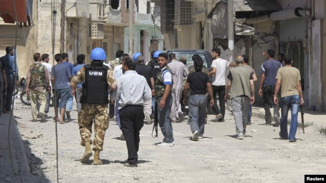 UN observers inspect a residential area with Free Syrian Army gunmen in the Talbisah area of Homs.