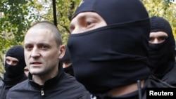 Сергей Удальцов в сопровождении бойцов спецназа