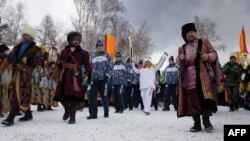 Surrounded by folks in traditional garb, torchbearer Akhmetova Svetlana (center) holds the torch aloft as the Olympic flame passes through the city of Irkutsk on the way to Sochi.