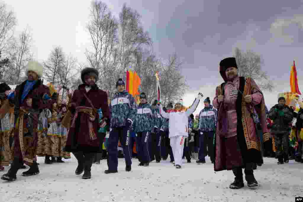Olympic torchbearer Akhmetova Svetlana (center) waves as she holds the torch with the Olympic flame in Irkutsk on November 23. Russia is hosting the 2014 Winter Olympics in the Caucasus city of Sochi. (AFP)
