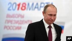 Президент России и кандидат в президенты Владимир Путин на избирательном участке в Москве. 18 марта 2018 года.