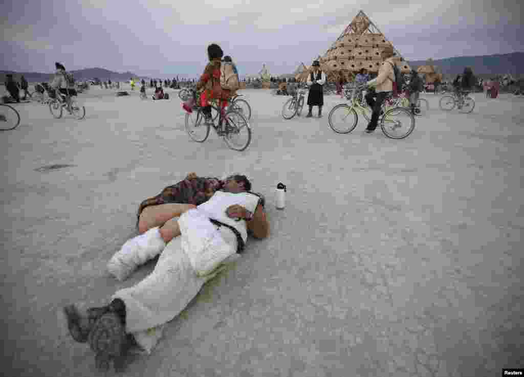"Participants cuddle at sunrise at the ""Temple of Whollyness"" during the Burning Man 2013 arts and music festival in the Black Rock Desert of Nevada."