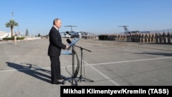 Russian President Vladimir Putin addresses Russian troops as he visits the Hmeimim military base on December 11.