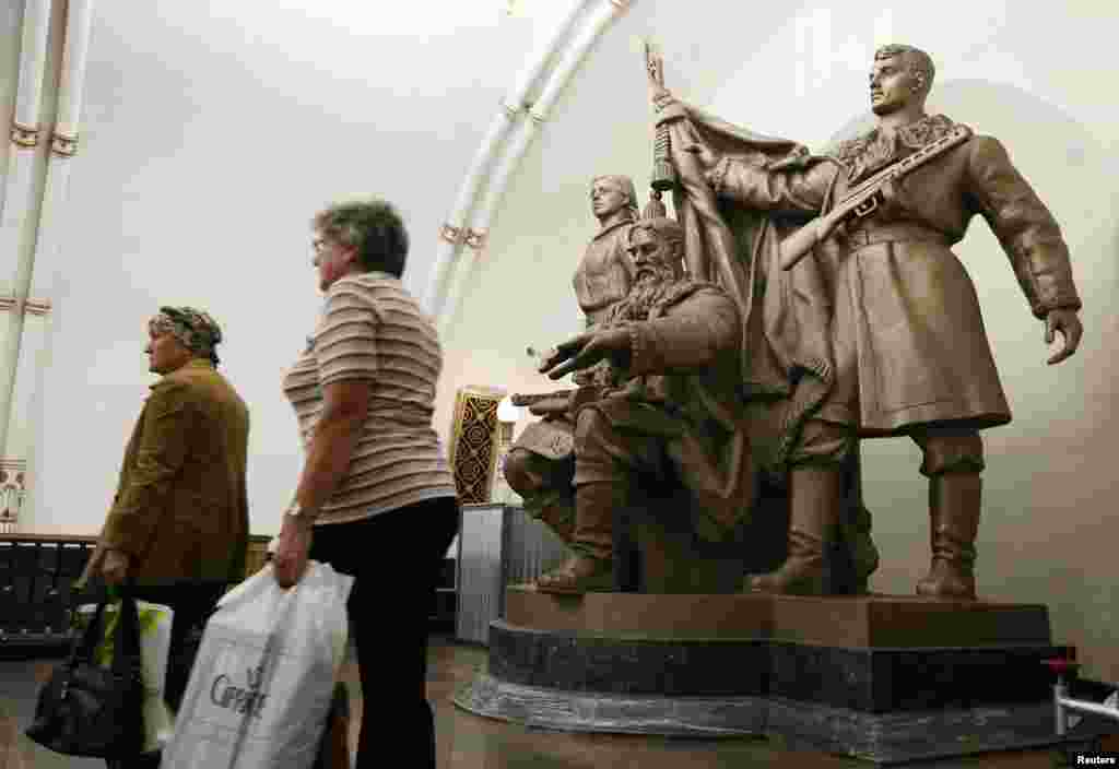 Women walk past a statue at the Belorusskaya metro station.