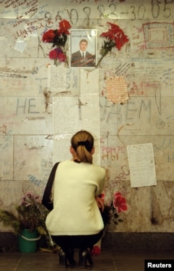 Дзяўчына ля сьцяны з партрэтам ахвяры цісканіны на Нямізе, 30 траўня 1999 году