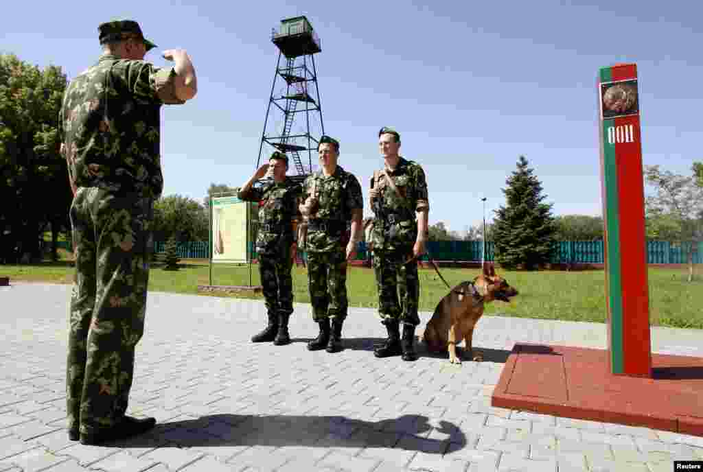Belarus border guards with a dog take orders before work at their base in the western city of Brest at the Belarus-Poland border