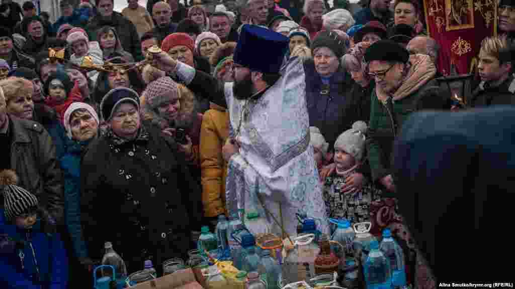 Жителі міста з дітьми під час молитви біля причалу