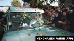 IRAN - An Iranian mourner layes red roses on the ambulance that carries the coffin of Iranian poet Ahmad Shamlou during his funeral in Tehran 27 July 2000