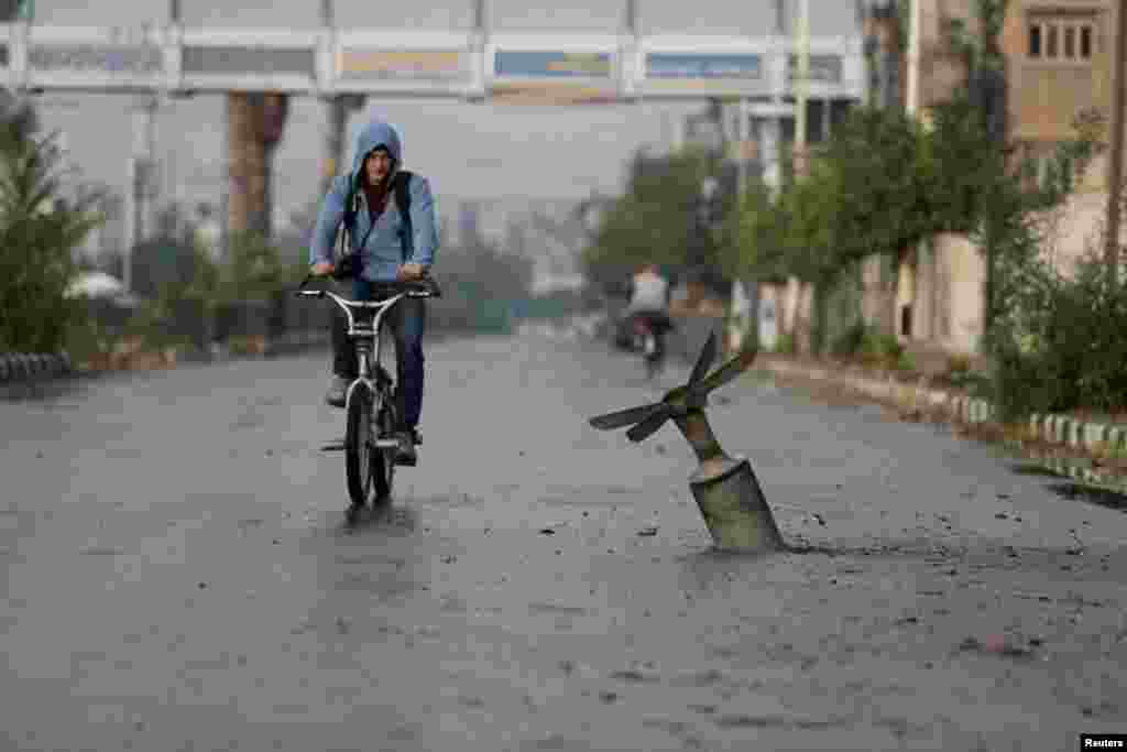 A resident rides his bicycle past what activists said was an exploded cluster bomb.