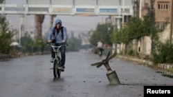 A resident rides his bicycle near what activists said was an exploded cluster bomb shell in the town of Douma, north-east of Damascus in November.