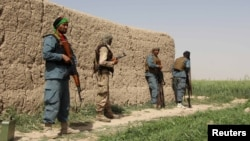 Afghan policemen keep watch during a battle with the Taliban in the Nahr-e Saraj district of Helmand Province on May 11.