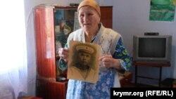 Sürgün olunğan Abibe Mustafayeva cenkte elâk olğan babasınıñ fotoresimi ile