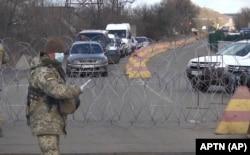 Український військовий зупиняє машини на блокпості в Майорську Донецької області, 16 березня 2020 року