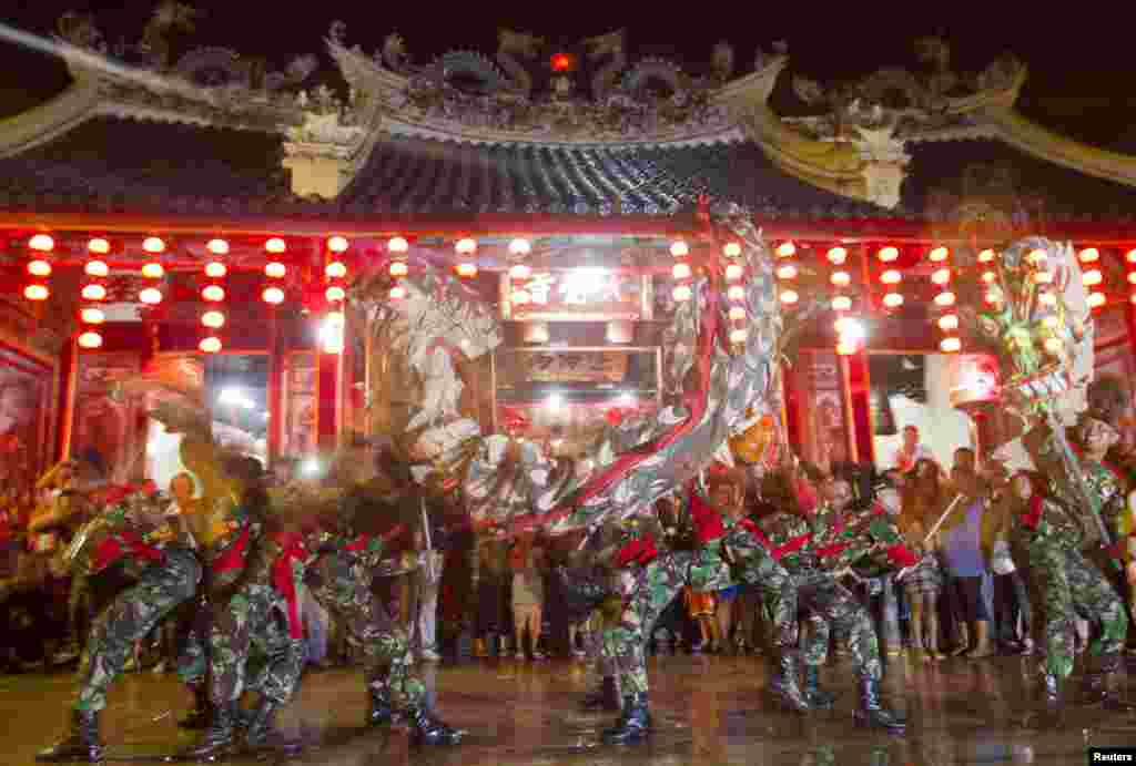 Soldiers perform a dragon dance in front of Tay Kei Sek temple in Semarang in central Java in Indonesia.