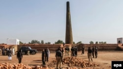 Pakistani Police inspect the brick kiln where a Christian couple was burnt alive for alleged blasphemy, in Kot Radha Kishan, near Kasur, on November 4, 2014.
