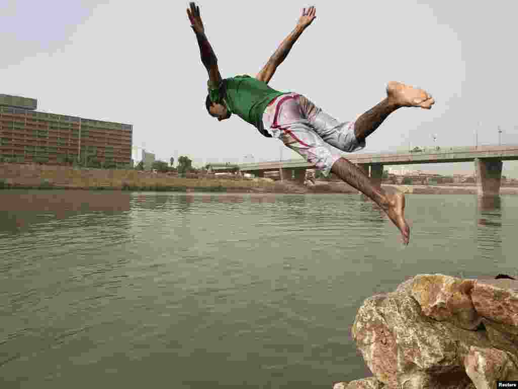 A boy jumps into the Tigris River for a swim on a warm summer day in Baghdad on July 14. Photo by Thaier al-Sudani for Reuters