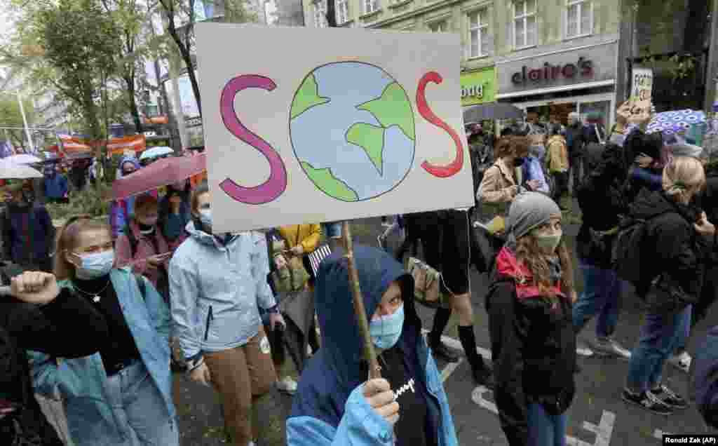 Environmental activists wearing face masks to help protect against the spread of the coronavirus stage during a rally marking the Global Day of Climate Action in Vienna, Austria, Friday, Sept. 25, 2020.