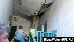 Разваливающуюся крышу в доме № 16 в Старом городе подпирают деревянными балками. Темиртау, 15 августа 2015 года.