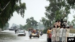 Residents evacuate from a waterlogged area of Humayun, near Jacobabad, today.