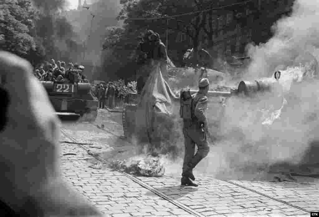 Soviet soldiers try to extinguish a burning tank set on fire by protesters near the Czechoslovak Radio headquarters in Prague.