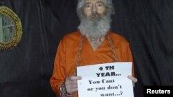 Зроблена в 2011 році фотографія, чоловік тримає в руках папір із текстом «Четвертий рік... Ви не можете чи не хочете?»