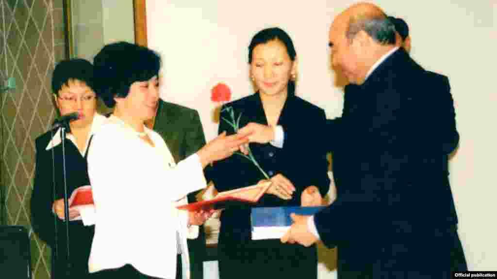 Бывший президент Аскар Акаев вручает цветы Бюбюкан Досалиевой.