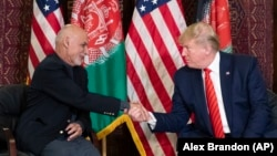 U.S. President Donald Trump meets with Afghan President Ashraf Ghani during a surprise visit to the country, at Bagram Air Field, in November 2019. Trump is pushing to withdraw more troops before the November vote in order to meet a campaign pledge.