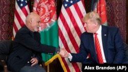 FILE: U.S. President Donald Trump shakes hands with Afghan President Ashraf Ghani at Bagram Air Field in November 2019.