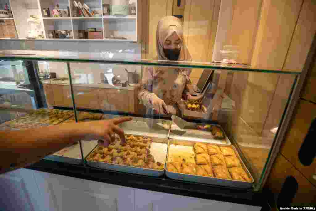 A shop attendant sells baklava to a customer ahead of Eid al-Adha in Pristina.