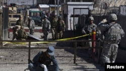 A policeman collects body parts after an attack at Camp Phoenix in Kabul on April 2.