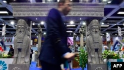 A visitor walks past a likeness of antique Persian statues at the Iran stand of the International Tourism Trade Fair (ITB, Internationale Tourismusboerse) in Berlin during the fair's opening day on March 7, 2018. - The business platform for global tourist