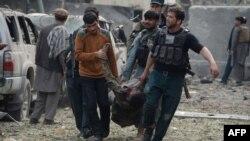 Афғонистондаги террор ҳужумларидан бирида яраланган одамни эвакуация қилиш пайтида олинган сурат.