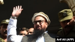 FILE: Hafiz Saeed waves to supporters as he leaves a court in Lahore in November 2017.
