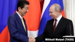 Japanese Prime Minister Shinzo Abe (left) and Russian President Vladimir Putin shake hands after a joint press statement following their meeting at the Kremlin in Moscow on January 22.