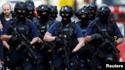 Armed police officers walk near Borough Market on June 4 after an attack left 7 people dead and dozens injured in London.