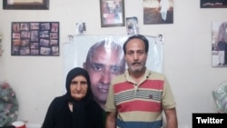 Zartosht Ahmadi Ragheb at his home near Tehran in August 2019. Behind him on the wall are photos of other imprisoned activists. File photo