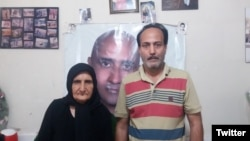 Zartosht Ahmadi Ragheb at his home near Tehran in August 2019. Behind him on the wall are photos of other imprisoned activists.