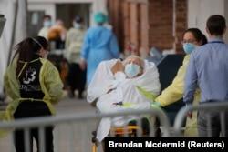 Парамедики доставляют пациента в центр неотложной помощи в Бруклинском районе, Нью-Йорк, США, 7 апреля 2020 года