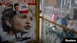 Ілюстраційне фото. Реклама обкладинки журналу з кандидатом в президенти Юлією Тимошенко та виборчого плаката кандидата в президенти Петра Порошенка на наступний день після президентських виборів в Києві, 26 травня 2014 року