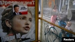 A woman pushes a child on a stroller past an advertisement for a magazine with presidential candidate Yulia Tymoshenko on the cover and an election sticker for current incumbent Petro Poroshenko.