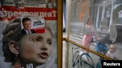 Предвыборные плакаты с изображениями кандиатов в президенты: бывшего премьера Юлии Тимошенко и действующего президента Петра Порошенко - на остановке в Киеве.