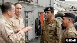 A U.S. Defense Department handout photo of Admiral Mike Mullen (left) with Pakistani army chief General Ashfaq Kayani (second from right) and ISI chief Major General Ahmad Shuja Pasha (right) aboard a U.S. warship in 2008