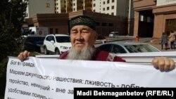 Житель Астаны Ибрагим Козыбаев развернул баннер в попытке провести одиночную акцию у здания Союза журналистов. Астана, 21 мая 2018 года.