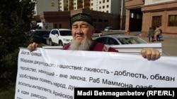 Астана тұрғыны Ибрагим Қозыбаев наразылық плакатын ұстап тұр. 21 мамыр 2018 жыл