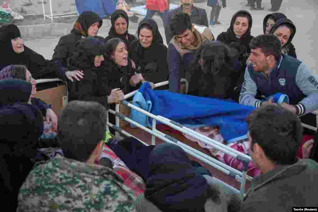 People react next to a dead body in Sarpol-e Zahab county in Kermanshah.