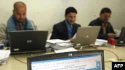 Electoral workers tally ballots at a center in central Baghdad.