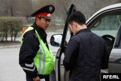 Автокөлік жүргізушісінің құжатын тексеріп тұрған полиция қызметкері.