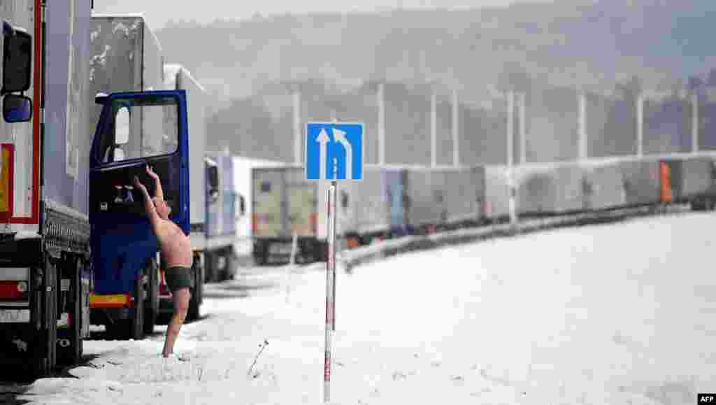 A truck driver does his morning exercises as his vehicle stands in line at the Belarusian-Lithuanian border, some 150 kilometers northwest of Minsk. (AFP/Yasin Akgul)